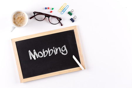 mobbing: Mobbing word on chalkboard with coffee cup and eyeglasses, view from above