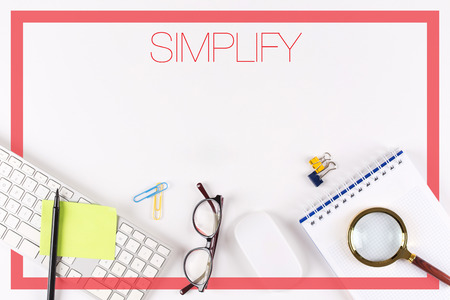simplification: High angle view of various office supplies on desk with a word SIMPLIFY