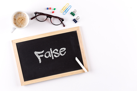 untrue: FALSE word on chalkboard with coffee cup and eyeglasses, view from above
