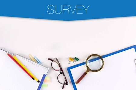 poll: High angle view of various office supplies on desk with a word SURVEY