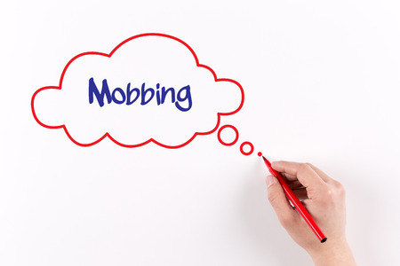 mobbing: Hand writing Mobbing on white paper, view from above Stock Photo