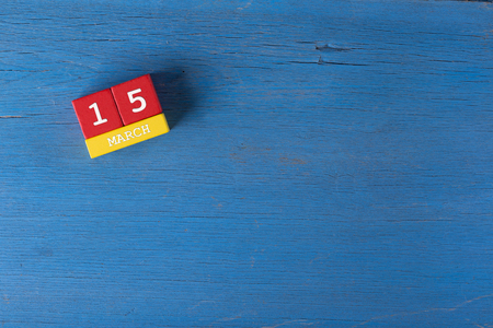 15 months old: March 15, Cube calendar on wooden surface with copy space