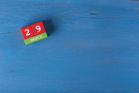 29: March 29, Cube calendar on wooden surface with copy space
