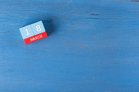 18 month old: March 18, Cube calendar on wooden surface with copy space