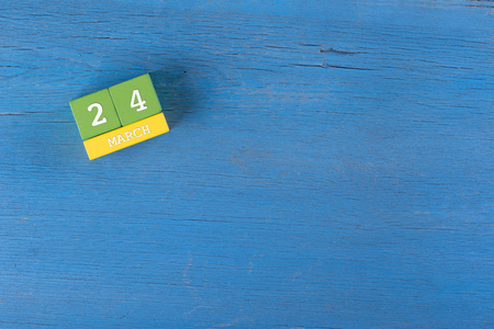 24 month old: March 24, Cube calendar on wooden surface with copy space