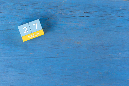 27 years old: March 27, Cube calendar on wooden surface with copy space