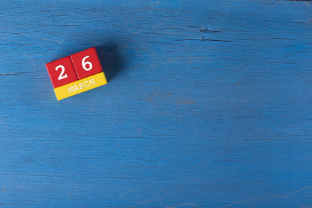 26: March 26, Cube calendar on wooden surface with copy space Stock Photo