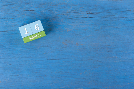 16: March 16, Cube calendar on wooden surface with copy space