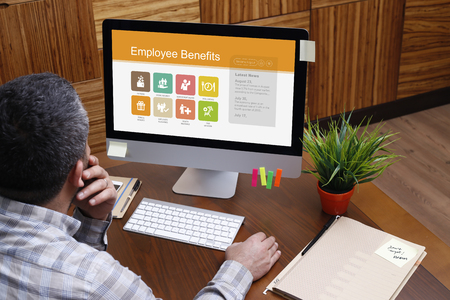 pay raise: Man using computer with Employee Benefits concept on screen Stock Photo