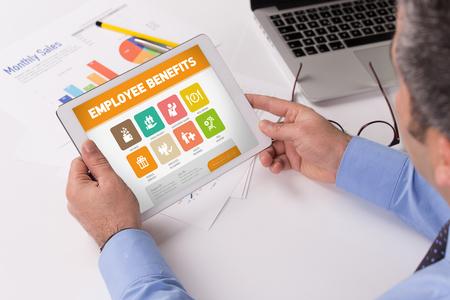 Homme travaillant sur une tablette avec des avantages sociaux sur un écran