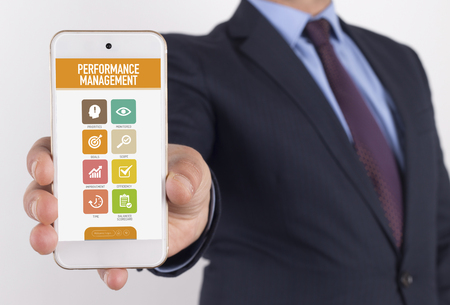 contributing: Man showing smartphone Performance Management on screen