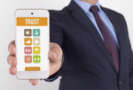 belief system: Man showing smartphone Trust on screen Stock Photo