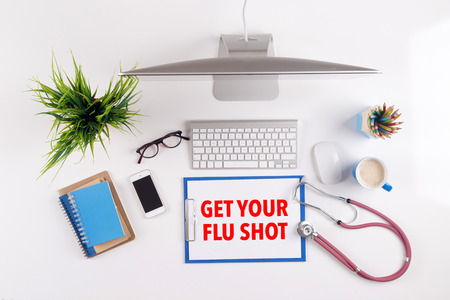 swine flu vaccinations: Office desk with GET YOUR FLU SHOT paperwork and other objects around, top view Stock Photo