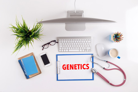 genomes: Office desk with GENETICS paperwork and other objects around, top view Stock Photo