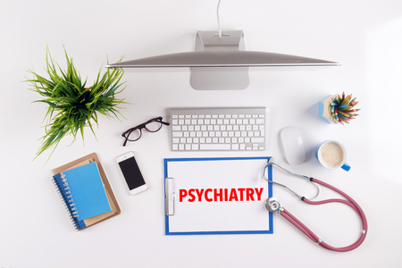 psychiatry: Office desk with PSYCHIATRY paperwork and other objects around, top view