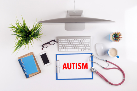 clinical psychology: Office desk with AUTISM paperwork and other objects around, top view
