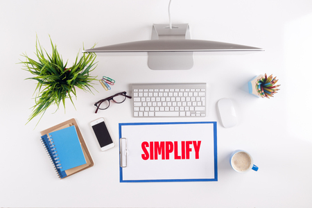 simplification: Office desk with SIMPLIFY paperwork and other objects around, top view