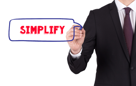 pragmatic: Hand writing a word SIMPLIFY on white board Stock Photo