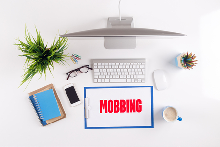mobbing: Office desk with MOBBING paperwork and other objects around, top view
