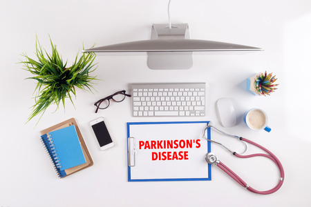 Office desk with PARKINSONS DISEASE paperwork and other objects around, top view