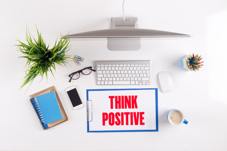 different goals: Office desk with THINK POSITIVE paperwork and other objects around, top view