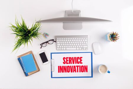 service desk: Office desk with SERVICE INNOVATION paperwork and other objects around, top view Stock Photo