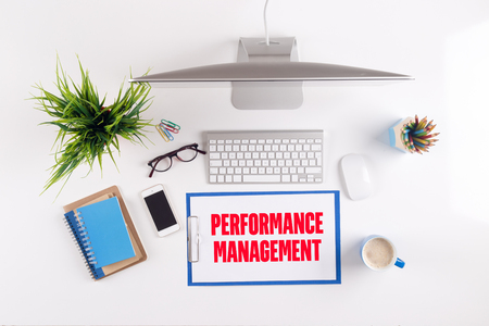 Office desk with PERFORMANCE MANAGEMENT paperwork and other objects around, top view Stock Photo
