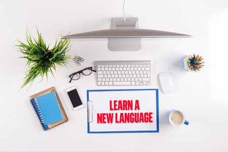 fluency: Office desk with LEARN A NEW LANGUAGE paperwork and other objects around, top view Stock Photo