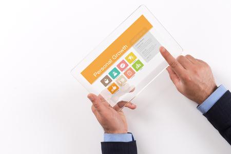 crecimiento personal: Mano que sostiene Tablet PC transparente con pantalla de Crecimiento Personal Foto de archivo