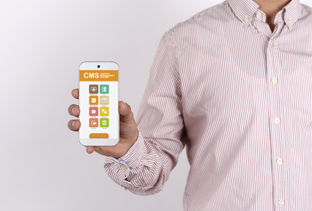management system: Man showing smartphone Content Management System on screen Stock Photo