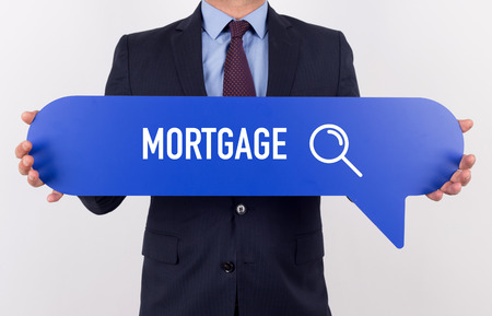 creditworthiness: Businessman holding speech bubble with a word MORTGAGE