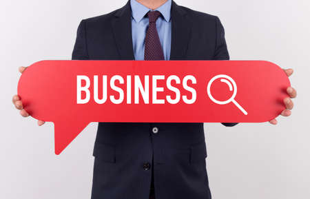 advertising space: Businessman holding speech bubble with a word BUSINESS