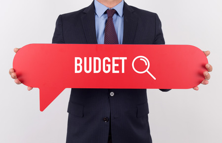 deficit target: Businessman holding speech bubble with a word BUDGET