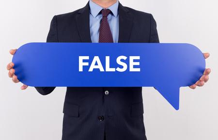 untrue: Businessman holding speech bubble with a word FALSE