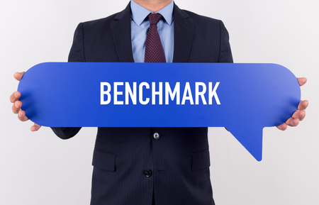benchmark: Businessman holding speech bubble with a word BENCHMARK