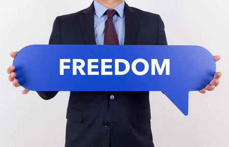 openness: Businessman holding speech bubble with a word FREEDOM Stock Photo