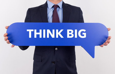 overachieving: Businessman holding speech bubble with a word THINK BIG