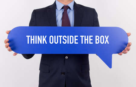 expressing artistic vision: Businessman holding speech bubble with a word THINK OUTSIDE THE BOX Stock Photo