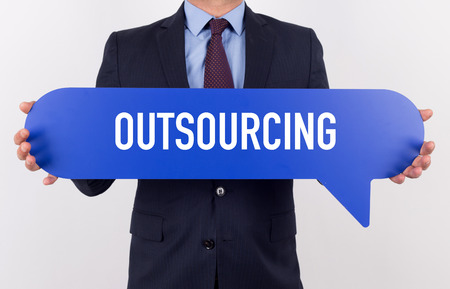 offshoring: Businessman holding speech bubble with a word OUTSOURCING