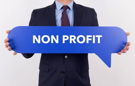 non: Businessman holding speech bubble with a word NON PROFIT