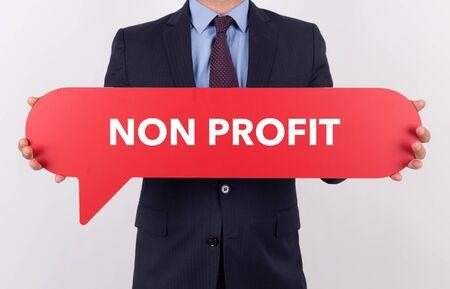 non profit: Businessman holding speech bubble with a word NON PROFIT