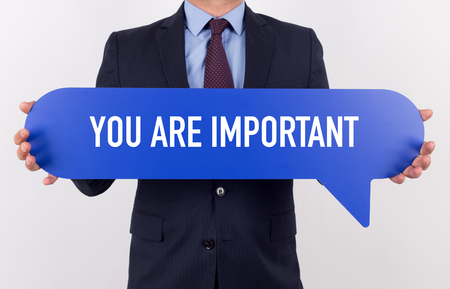 self assurance: Businessman holding speech bubble with a word YOU ARE IMPORTANT Stock Photo