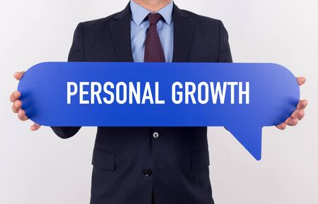 crecimiento personal: Businessman holding speech bubble with a word PERSONAL GROWTH
