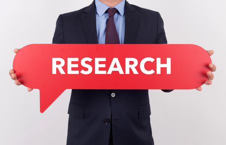 hip�tesis: Businessman holding speech bubble with a word RESEARCH