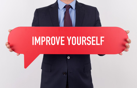 alteration: Businessman holding speech bubble with a word IMPROVE YOURSELF Stock Photo
