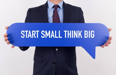 Businessman holding speech bubble with a word START SMALL THINK BIG