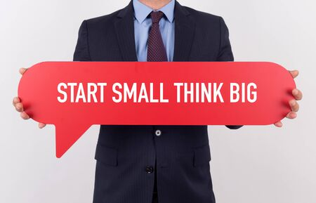 surpass: Businessman holding speech bubble with a word START SMALL THINK BIG