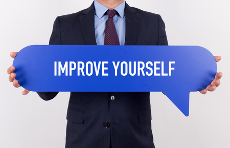 enrich: Businessman holding speech bubble with a word IMPROVE YOURSELF Stock Photo