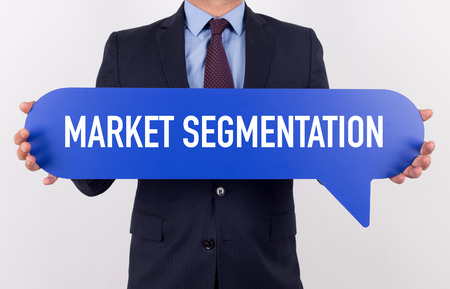 segmentation: Businessman holding speech bubble with a word MARKET SEGMENTATION Stock Photo