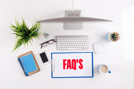 faq's: Office desk with FAQS paperwork and other objects around, top view Stock Photo